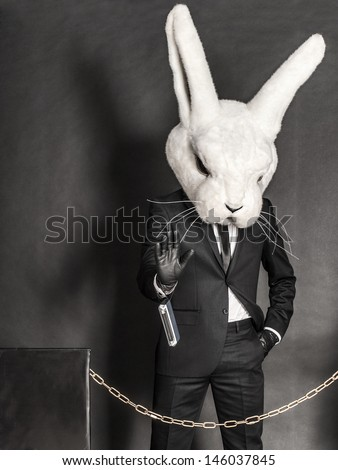 man in black suit inside rabbit face mask stay on face control on gray background