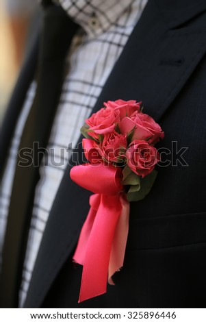 Man in black suit jacket with one small beautiful colorful soft aroma fresh wedding bouquet posy of many red rose flowers outdoor on checkered shirt background, vertical picture