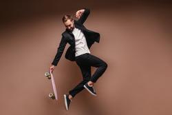 Man in black suit jumps on skateboard on brown background