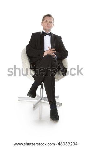 man in black suit sitting in an armchair
