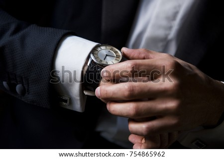 Man in black suit wear new watches. Luxury style Hand of a man in a black suit with a watch\ Man in a suit adjusts his black watch on the wirst