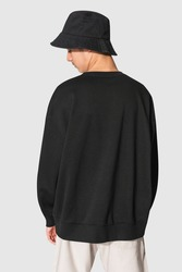 Man in black sweater and black bucket hat teen's apparel shoot