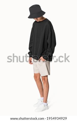 Man in black sweater and black bucket hat teenage apparel shoot
