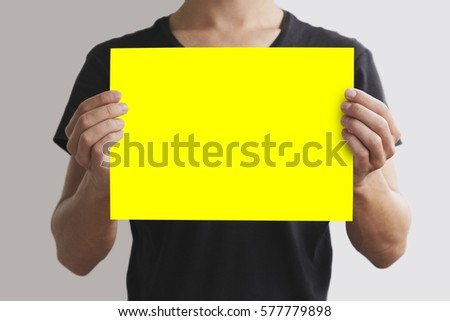 Man in black t shirt holding blank yellow A4 paper horizontally. Leaflet  presentation. Pamphlet