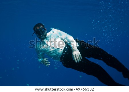 man in black trousers, white shirt and bow tie cruising through blue water. - stock photo