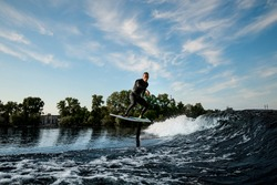 man in black wetsuit is vigorously riding the wave on foilboard on background of blue sky and trees