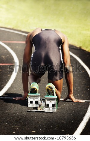 Man in blocks on the starting line of a race (main focus on shoes and blocks)