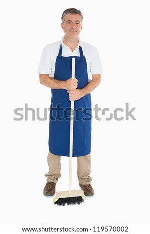 Man in blue apron holding sweeping brush