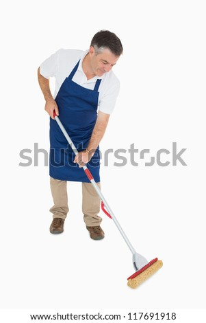 Man in blue apron mopping the floor