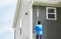 Man in blue jacket clean dusk and dirt from exterior siding and under roof by high-pressure nozzle spray with water soap cleaner, weekend chore on sunny day. Cleansing and maintenance service concept.