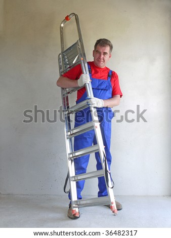 Man in blue jumpsuit holding aluminum ladder in room with newly plastered walls