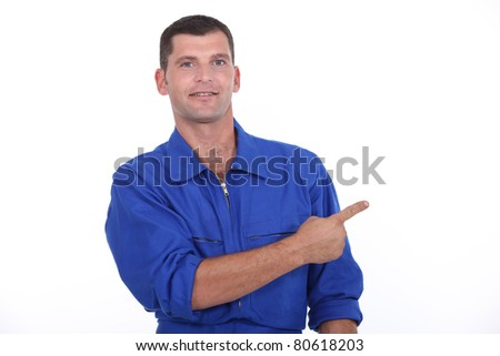 Man in blue overalls pointing - stock photo