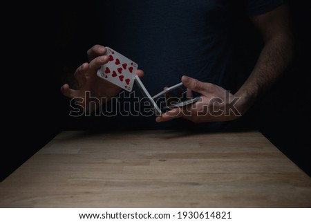 Man in blue shirt against dark background shuffling a deck of red cards at a wooden table. Games cards playing poker gambling. Foto stock ©