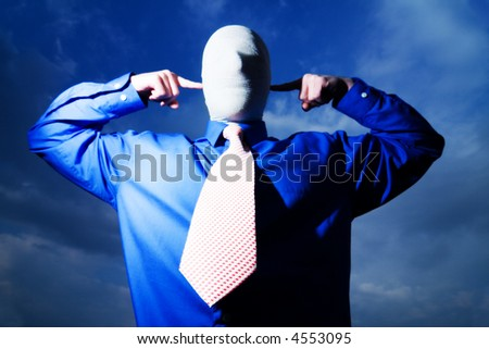 Man in blue shirt and necktie, face and head wrapped,fingers pointing at ears, blue sky background
