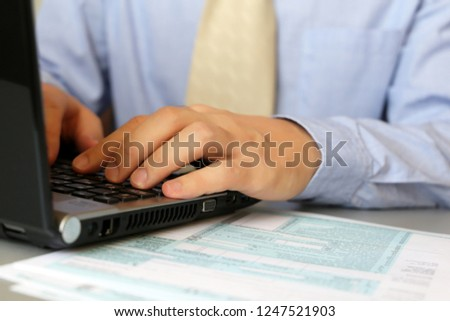 Man in blue shirt and tie works, sitting at a table with laptop. Male hands typing on keyboard, concept of office manager, staffing, broker, businessman or bank employee, using notebook