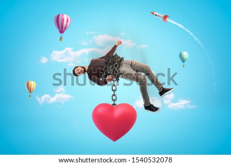 Man in blue sky bound with chains to huge red heart which is pulling him down. Dating and relationship. Problems in relationship. Possessive relationship.