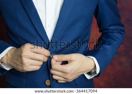 Man in blue suit two buttons, doing button