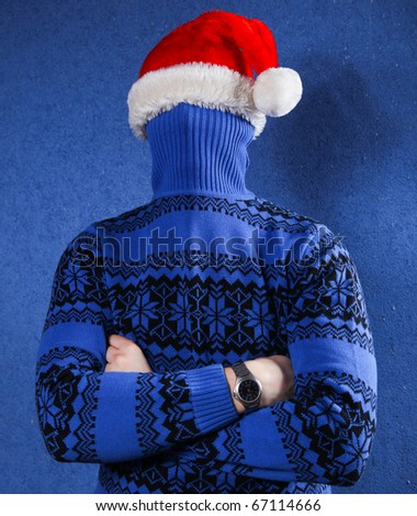 Man in blue sweater and red chrismas hat at blue background