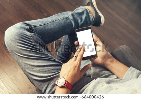 Shutterstock Man in bluejeans wearing a red watch and a ring is using a smart phone seated with crossed legs, fingers pointed to the screen, white screen isolated for commercial, point of view from top, no head