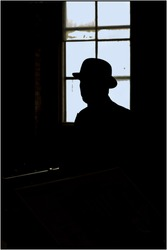 Man in bowler hat looking left