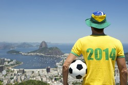 Man in Brazil hat and 2014 shirt standing with football bright sunny Rio de Janeiro skyline with Sugarloaf Pao de Acucar Mountain