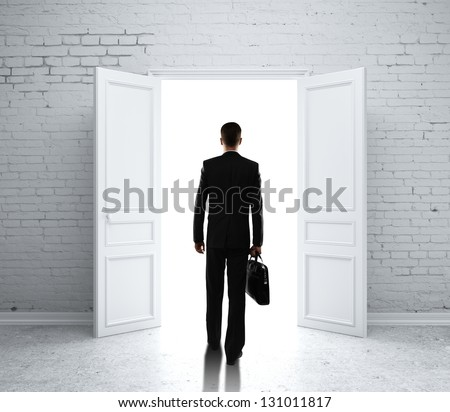 man in brick room with open door