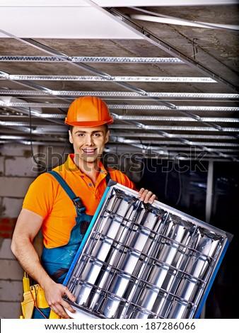 Man in builder uniform installing suspended ceiling