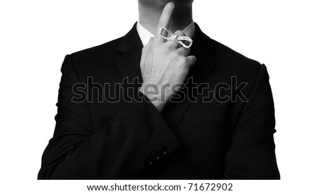 man in buisness suit with a knot around his finger to make him remember something!