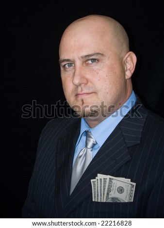 Man in business suit against dark background with several one-hundred dollar bills
