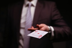 Man in business suit catche red ace playing card. Owning gambling business, maintaining casino and slot machine hall. Illusionist demonstrate trick.