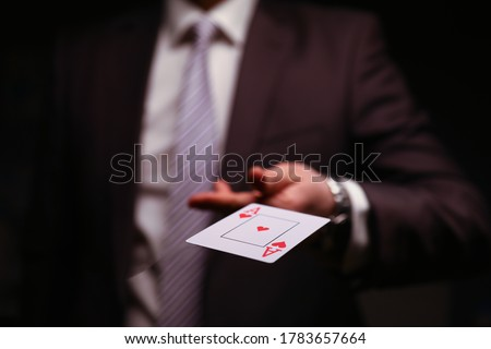 Man in business suit catche red ace playing card. Owning gambling business, maintaining casino and slot machine hall. Illusionist demonstrate trick. ストックフォト ©