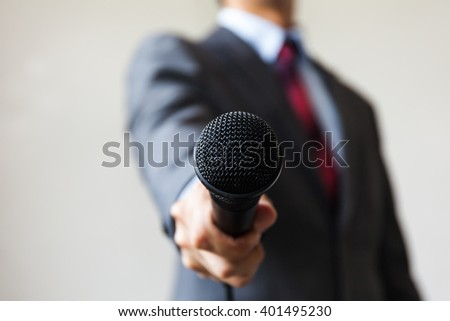 Man in business suit holding a microphone conducting a business interview, journalist reporting, public speaking, press conference, MC #401495230