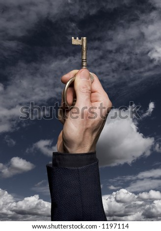 Man in business suit holding an antique key against a blue sky with clouds.