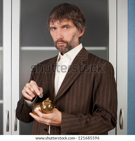 man in business suit puts coin in a piggy bank
