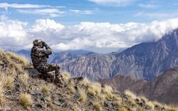 Man in camouflage on the slope is watching through binoculars in the mountains. Hunter looks through binoculars against the background of the sky and mountain landscape.