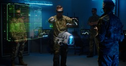 Man in camouflage uniform and goggles using controllers to operate modern military UAV