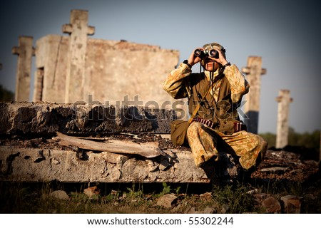 Man in camouflage uniform is looking through the binoculars. Urban ruins on the background.