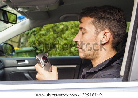 Man in car looking at breathalyzer - stock photo