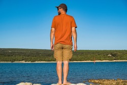 Man in cargo pants standing on sea shore and observing the surface, Losinj island, Croatia