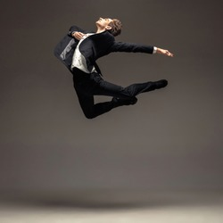 Man in casual office style clothes jumping and dancing isolated on grey background. Art, motion, action, flexibility, inspiration concept. Flexible caucasian ballet dancer, weightless jumps.