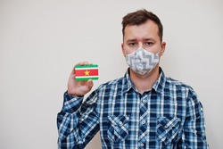 Man in checkered shirt show Suriname flag card in hand, wear protect mask isolated on white background. American countries Coronavirus concept.