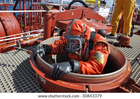 man in chemical suit entering inside  cargo tank on chemical ship for cleaning operation