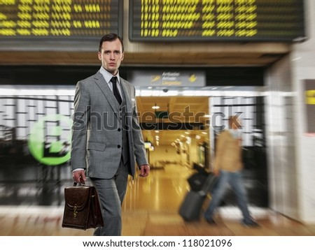 Man in classic grey suit with briefcase in airport