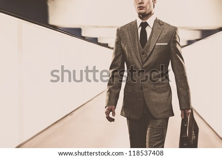 Man in classic suit with briefcase walking through corridor