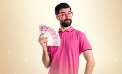 Man in colorful clothes taking a lot of money on ocher background