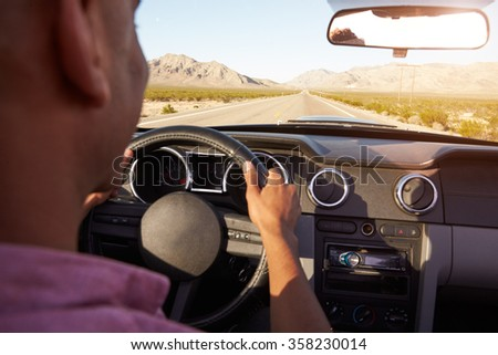 Man In Convertible Car Driving Along Open Road