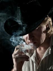 Man in cowboy hat is smoking a cigarette in dark