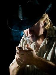 Man in cowboy hat lights a cigarette in dark