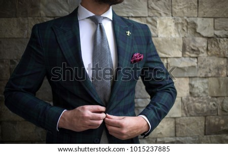 Man in custom tailored suit posing in front of wall and buttoning his jacket