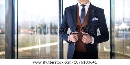 Man in custom tailored suit posing indoors